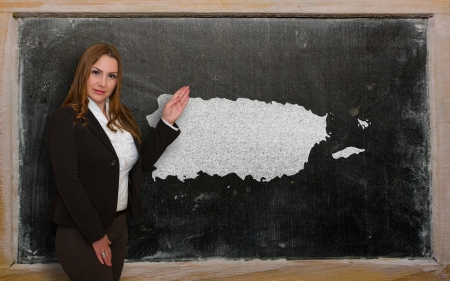 Successful, beautiful and confident young woman showing map of puerto rico on blackboard for presentation, marketing research and tourist advertising