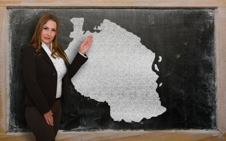 Successful, beautiful and confident young woman showing map of tanzania on blackboard for presentation, marketing research and tourist advertising photo