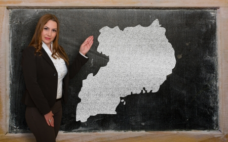 Successful, beautiful and confident young woman showing map of uganda on blackboard for presentation, marketing research and tourist advertising photo