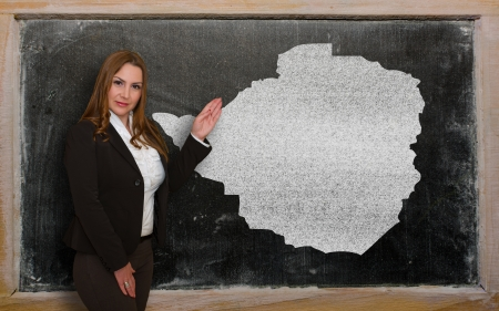 Successful, beautiful and confident young woman showing map of zimbabwe on blackboard for presentation, marketing research and tourist advertising photo