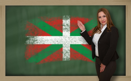 basque woman: Successful, beautiful and confident woman showing flag of basque on blackboard for marketing research, presentation and tourist advertising
