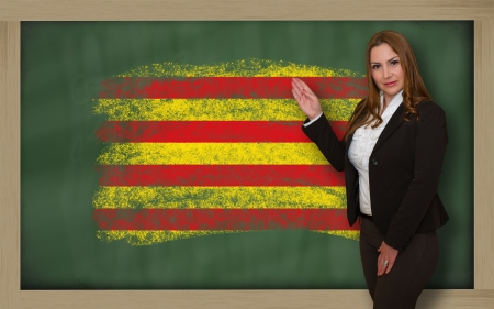 catalonian: Successful, beautiful and confident woman showing flag of catalonia on blackboard for marketing research, presentation and tourist advertising Stock Photo