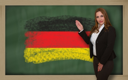 succesful woman: Successful, beautiful and confident woman showing flag of germany on blackboard for marketing research, presentation and tourist advertising Stock Photo