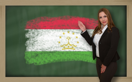 tajikistan: Successful, beautiful and confident woman showing flag of tajikistan on blackboard for marketing research, presentation and tourist advertising