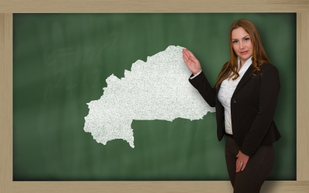 Successful, beautiful and confident young woman showing map of burkina faso on blackboard for presentation, marketing research and tourist advertising photo