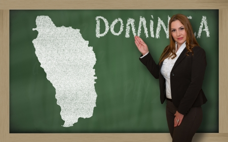 Successful, beautiful and confident young woman showing map of dominica on blackboard for presentation, marketing research and tourist advertising photo