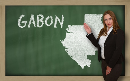 Successful, beautiful and confident young woman showing map of gabon on blackboard for presentation, marketing research and tourist advertising photo