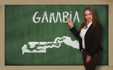 Successful, beautiful and confident young woman showing map of gambia on blackboard for presentation, marketing research and tourist advertising photo
