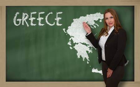 Successful, beautiful and confident young woman showing map of greece on blackboard for presentation, marketing research and tourist advertising photo