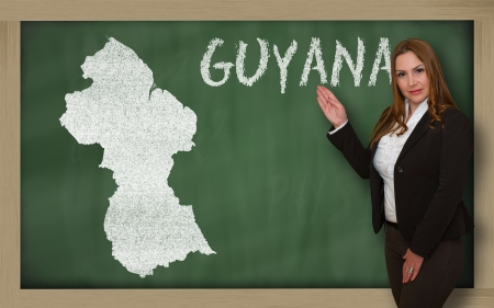 guyanese: Successful, beautiful and confident young woman showing map of guyana on blackboard for presentation, marketing research and tourist advertising