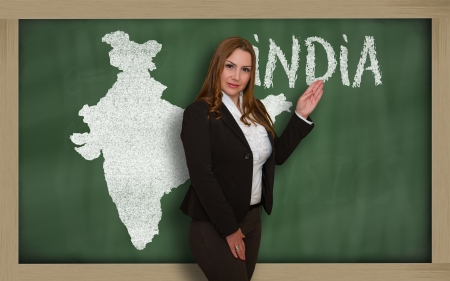 Successful, beautiful and confident young woman showing map of india on blackboard for presentation, marketing research and tourist advertising photo