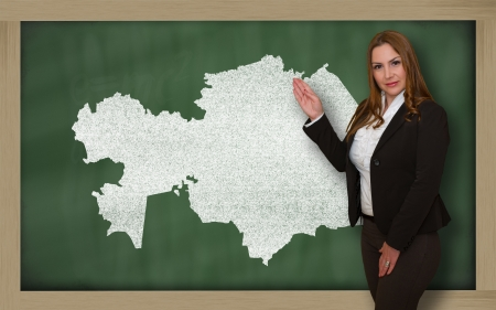 Successful, beautiful and confident young woman showing map of kazakhstan on blackboard for presentation, marketing research and tourist advertising