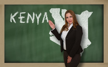 Successful, beautiful and confident young woman showing map of kenya on blackboard for presentation, marketing research and tourist advertising photo