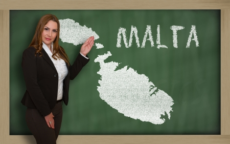 maltese map: Successful, beautiful and confident young woman showing map of malta on blackboard for presentation, marketing research and tourist advertising