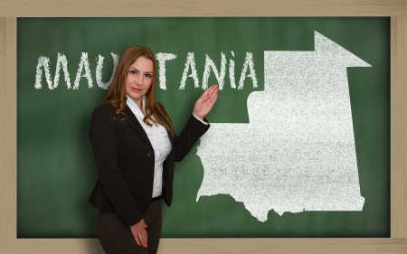 Successful, beautiful and confident young woman showing map of mauritania on blackboard for presentation, marketing research and tourist advertising photo