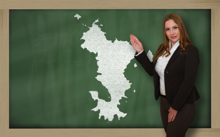 Successful, beautiful and confident young woman showing map of mayotte on blackboard for presentation, marketing research and tourist advertising photo