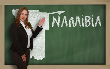 Successful, beautiful and confident young woman showing map of namibia on blackboard for presentation, marketing research and tourist advertising photo