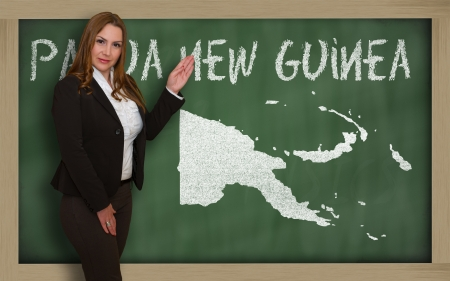 papua: Successful, beautiful and confident young woman showing map of papua new guinea on blackboard for presentation, marketing research and tourist advertising Stock Photo