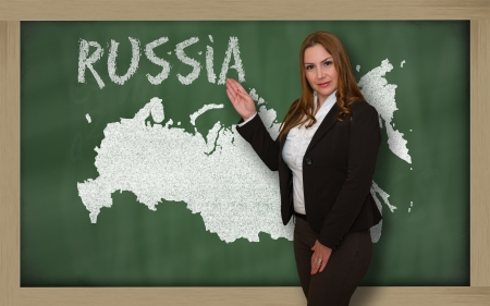Successful, beautiful and confident young woman showing map of russia on blackboard for presentation, marketing research and tourist advertising photo