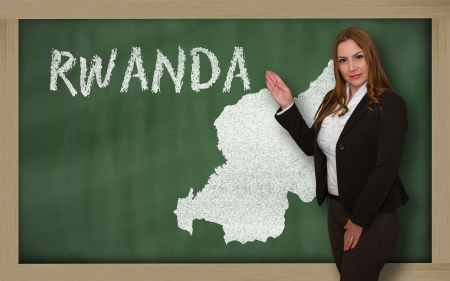 Successful, beautiful and confident young woman showing map of rwanda on blackboard for presentation, marketing research and tourist advertising photo