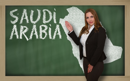 Successful, beautiful and confident young woman showing map of saudi arabia on blackboard for presentation, marketing research and tourist advertising photo