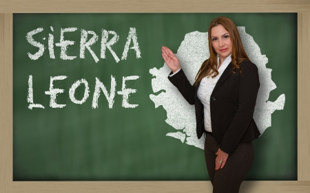 Successful, beautiful and confident young woman showing map of sierra leone on blackboard for presentation, marketing research and tourist advertising photo