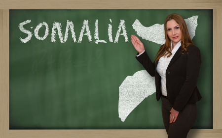 Successful, beautiful and confident young woman showing map of somalia on blackboard for presentation, marketing research and tourist advertising photo