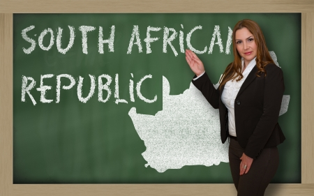 Successful, beautiful and confident young woman showing map of south africa on blackboard for presentation, marketing research and tourist advertising photo