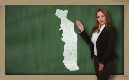 Successful, beautiful and confident young woman showing map of togo on blackboard for presentation, marketing research and tourist advertising photo