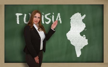Successful, beautiful and confident young woman showing map of tunisia on blackboard for presentation, marketing research and tourist advertising photo