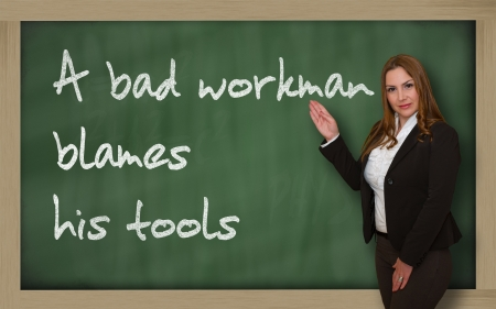 lack of confidence: Successful, beautiful and confident woman showing A bad workman blames his tools on blackboard
