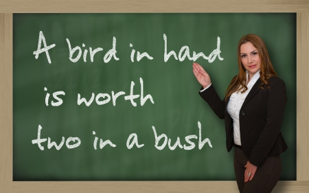 wriiting: Successful, beautiful and confident woman showing A bird in hand is worth two in a bush on blackboard