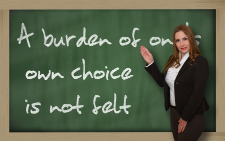 Successful, beautiful and confident woman showing A burden of ones own choice is not felt on blackboard photo
