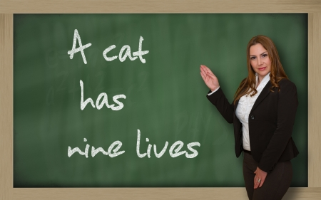 has: Successful, beautiful and confident woman showing A cat has nine lives on blackboard Stock Photo