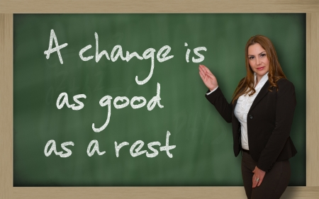 wriiting: Successful, beautiful and confident woman showing A change is as good as a rest on blackboard
