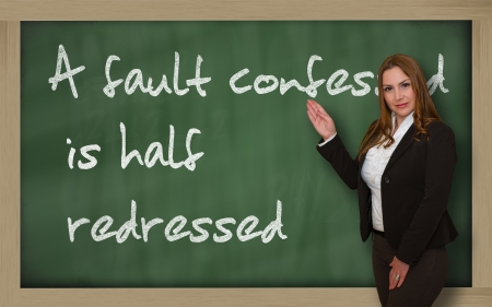 Successful, beautiful and confident woman showing A fault confessed is half redressed on blackboard Stock Photo