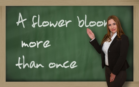 redeem: Successful, beautiful and confident woman showing A flower blooms more than once on blackboard Stock Photo