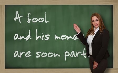 wriiting: Successful, beautiful and confident woman showing A fool and his money are soon (easily) parted on blackboard Stock Photo