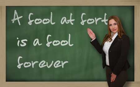 wriiting: Successful, beautiful and confident woman showing A fool at forty is a fool forever on blackboard Stock Photo