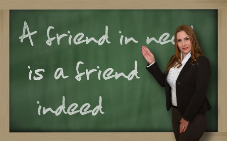 indeed: Successful, beautiful and confident woman showing A friend in need is a friend indeed on blackboard