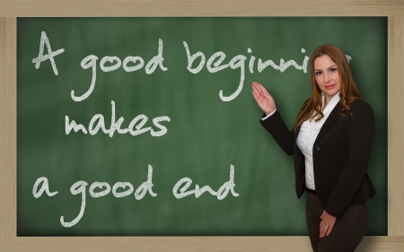 Successful, beautiful and confident woman showing A good beginning makes a good end on blackboard photo