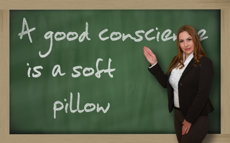 wriiting: Successful, beautiful and confident woman showing A good conscience is a soft pillow on blackboard