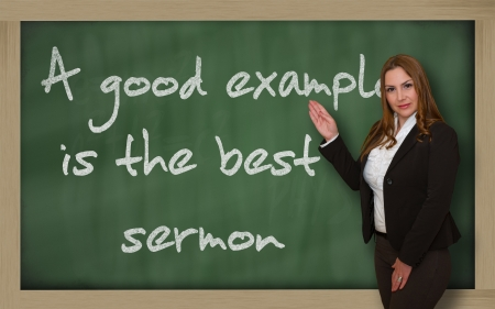 Successful, beautiful and confident woman showing A good example is the best sermon on blackboard