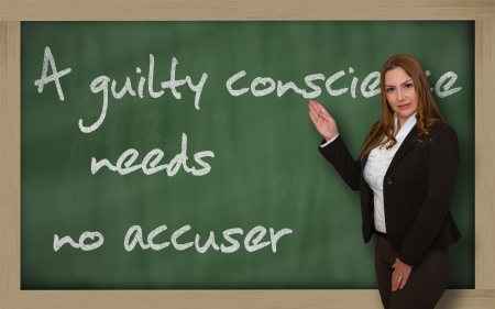 accuser: Successful, beautiful and confident woman showing A guilty conscience needs no accuser on blackboard Stock Photo