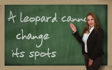 wriiting: Successful, beautiful and confident woman showing A leopard cannot change its spots on blackboard