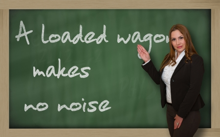 Successful, beautiful and confident woman showing A loaded wagon makes no noise on blackboard Stock Photo