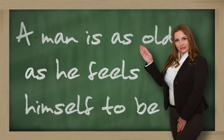 he: Successful, beautiful and confident woman showing A man is as old as he feels himself to be on blackboard Stock Photo