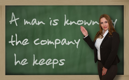 Successful, beautiful and confident woman showing A man is known by the company he keeps on blackboard Stock Photo - 18660427