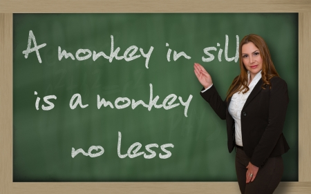 wriiting: Successful, beautiful and confident woman showing A monkey in silk is a monkey no less on blackboard