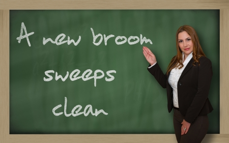 wriiting: Successful, beautiful and confident woman showing A new broom sweeps clean on blackboard Stock Photo